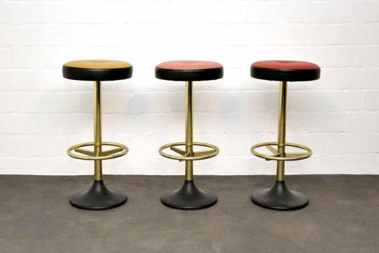 Drei Barhocker, rot gelb und lachsfarbene Kunstledersitze auf Metallgestellen